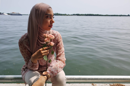 Girl sitting by the water with roses wearing a wooden watch
